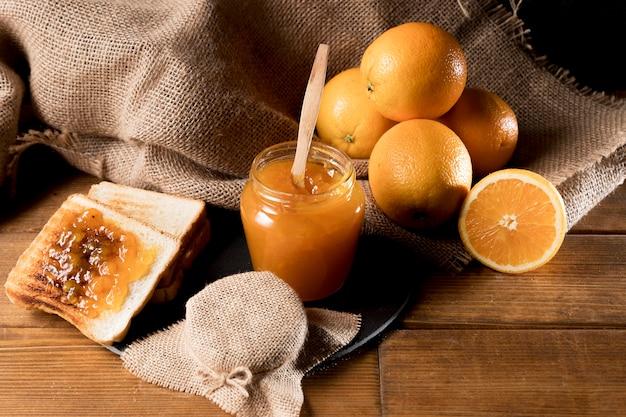 Hoher winkel des orangenmarmeladenglases mit brot