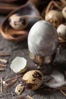 Hoher winkel des ostereies im eleganten eierbecher mit gebrochenen schalen