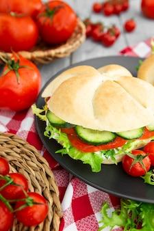 Hoher winkel des sandwichs auf teller mit vielen tomaten