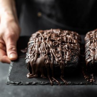 Hoher winkel des schokoladenkuchens, der vom konditor gehalten wird