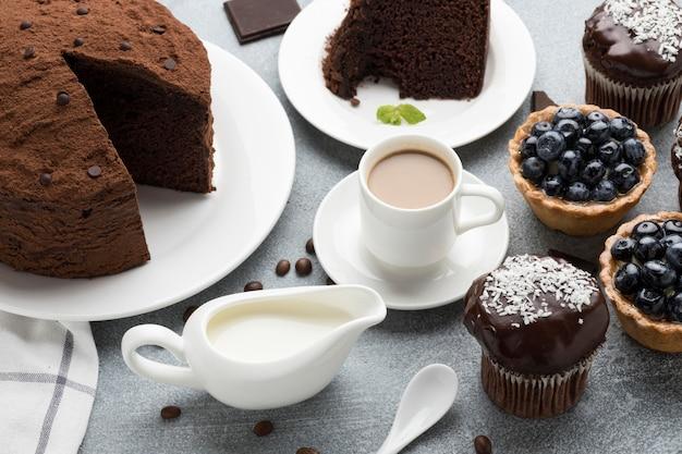 Hoher winkel des schokoladenkuchens mit blaubeertörtchen und kaffee