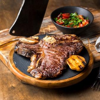 Hoher winkel des steaks auf teller mit salat und hackmesser