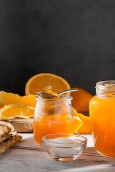 Hoher winkel des transparenten glases mit orangefarbener marmelade mit kopierraum