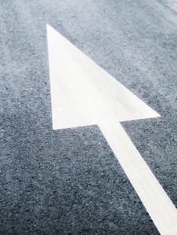 Hoher winkel des weißen pfeils auf asphalt, der zur linken oberen ecke zeigt