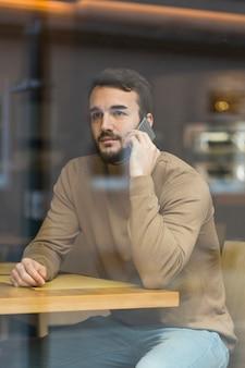 Hoher winkel junger geschäftsmann, der über telefon spricht