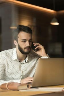 Hoher winkel junger unternehmer, der über telefon spricht