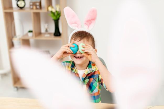Hoher winkel kleiner junge, der mit eiern spielt