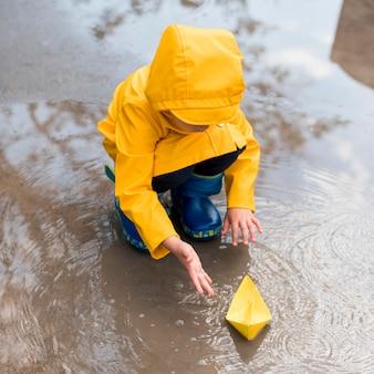 Hoher winkel kleiner junge, der mit einem papierboot spielt