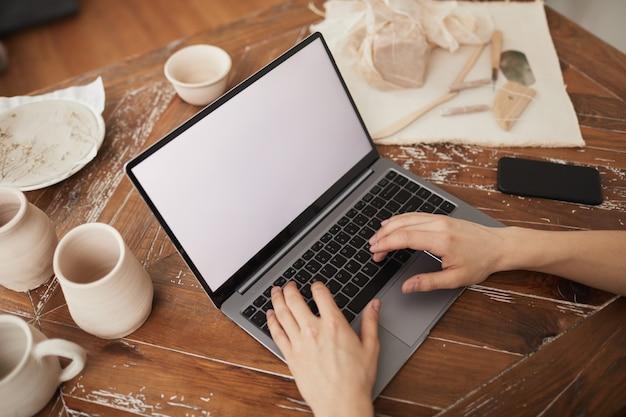 Hoher winkel nahaufnahme von männlichen händen, die auf laptop mit leerem weißem bildschirm am schreibtisch in der werkstatt tippen, konzept für kleine unternehmen, kopierraum