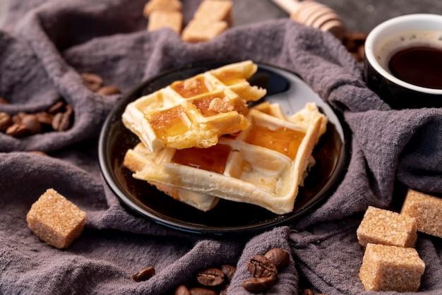 Hoher winkel von den waffeln bedeckt im honig auf platte mit zuckerwürfeln