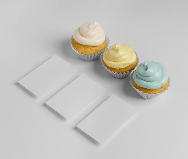 Hoher winkel von drei cupcakes mit verpackung und kopierraum