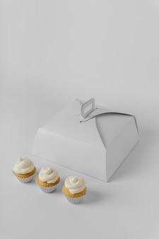 Hoher winkel von drei cupcakes mit verpackungsbox und kopierraum