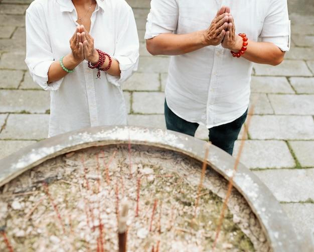 Hoher winkel von frau und mann, die am tempel mit brennendem weihrauch beten