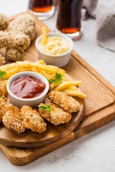 Hoher winkel von gebratenen hähnchenschenkeln und nuggets mit kohlensäurehaltigen getränken und pommes frites