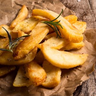Hoher winkel von gesalzenen pommes frites mit kräutern