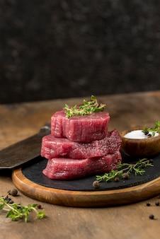 Hoher winkel von gestapeltem fleisch mit kräutern und kopierraum