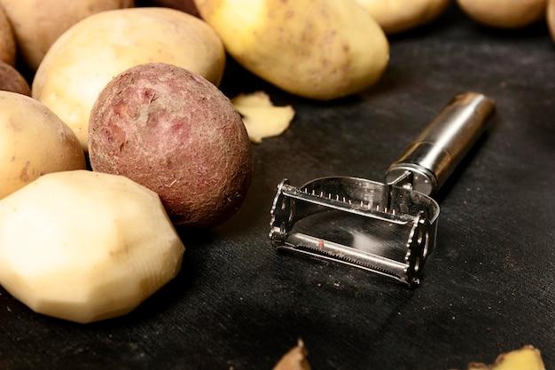 Hoher winkel von kartoffeln und schäler