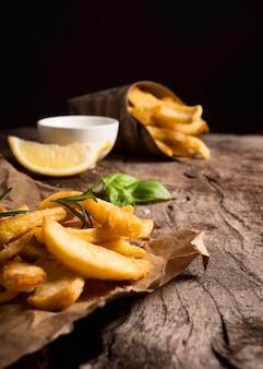 Hoher winkel von pommes frites auf papier mit sauce