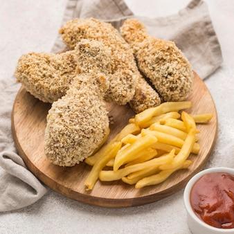 Hoher winkel von pommes frites mit gebratenen hähnchenschenkeln und sauce
