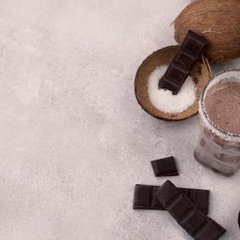 Hoher winkel von schokoladenmilchshake-glas mit kokosnuss und kopierraum