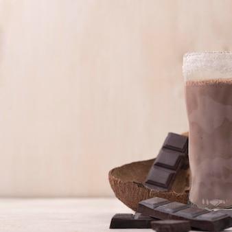 Hoher winkel von schokoladenmilchshake-glas mit kopierraum und kokosnuss