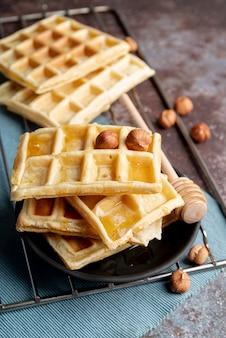 Hoher winkel von waffeln auf platte mit honigschöpflöffel und -haselnüssen