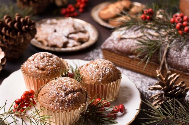 Hoher winkel von weihnachtscupcakes mit keksen und tannenzapfen