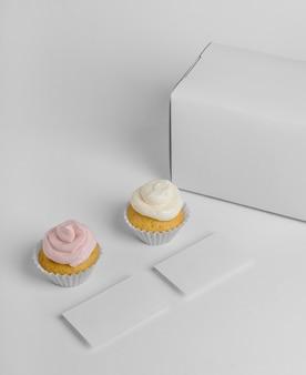 Hoher winkel von zwei cupcakes mit verpackungsbox