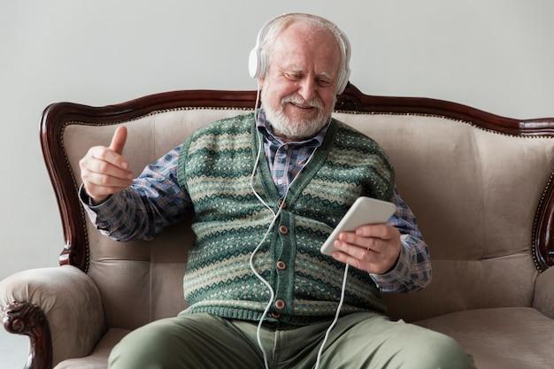 Hoher winkelältester auf der couch, die musik am telefon spielt