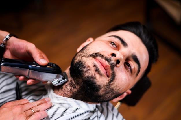 Hoher winkelfriseur, der den bart des kunden rasiert