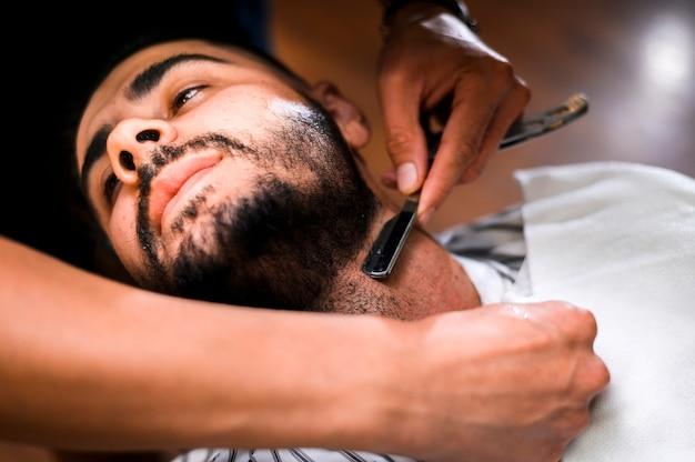 Hoher winkelfriseur, der den bart des mannes rasiert