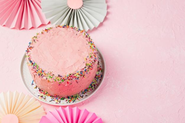 Hoher winkelrahmen mit rosa kuchen und kopieraum