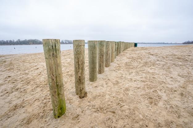 Hoher winkelschuss der hölzernen wellenbrecherstangen auf einem strandsand