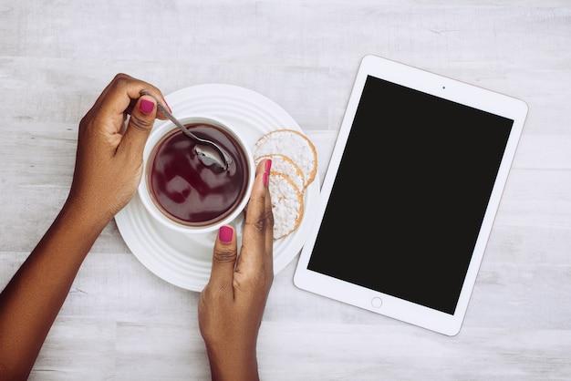 Hoher winkelschuss einer frau, die eine tasse tee mit keksen und einer tablette auf der seite hält