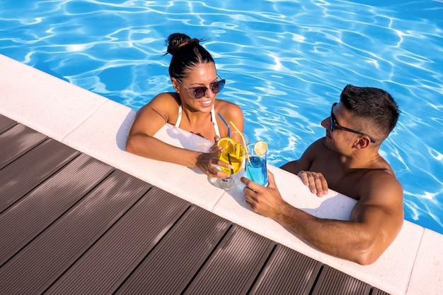 Hoher winkelschuss einer lächelnden gruppe eines paares, das cocktails im schwimmbad hält