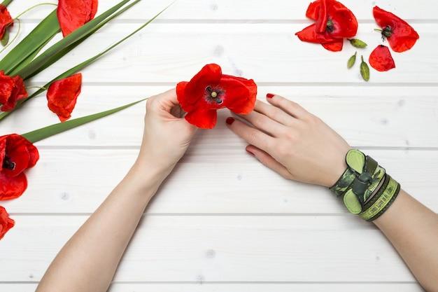Hoher winkelschuss einer person, die eine rote mohnblume auf einem holztisch hält