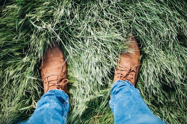 Hoher winkelschuss einer person, die lederschuhe und jeans trägt, die auf einem grasfeld stehen