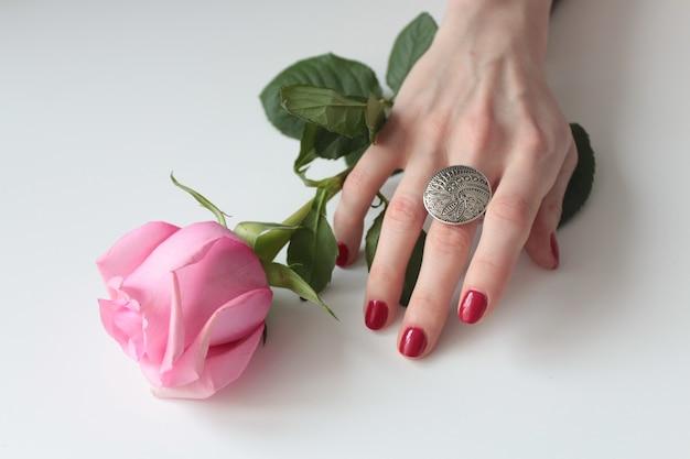 Hoher winkelschuss einer weiblichen hand mit einem schönen silbernen ring auf einer rose mit grünen blättern
