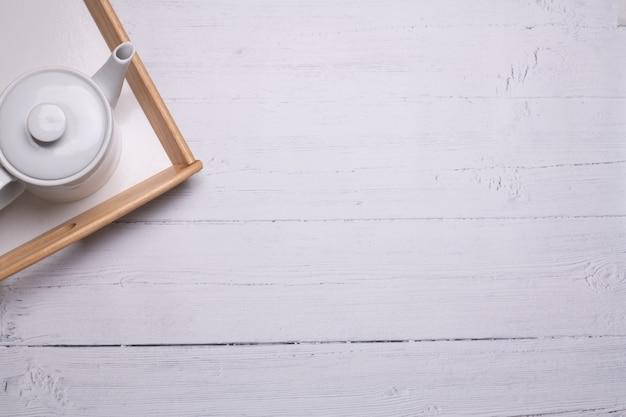 Hoher winkelschuss einer weißen teekanne auf einem tablett auf einem weißen holztisch