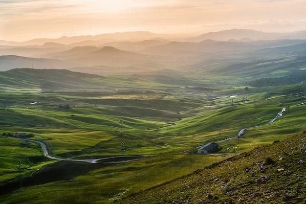 Hoher winkelschuss eines isolierten gebäudes in einem grünen feld, das von hohen bergen umgeben ist