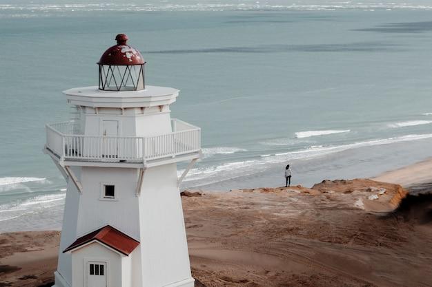 Hoher winkelschuss eines schönen leuchtturms am strand mit blick auf den ozean