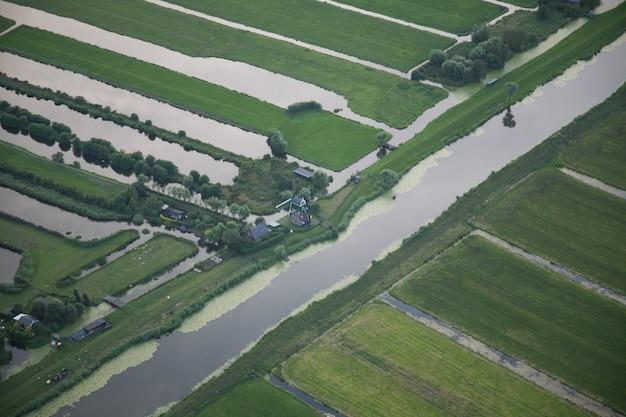Hoher winkelschuss eines wasserstroms in der mitte des grasfeldes am holländischen polder