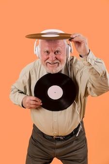Hoher winkelsmileyälterer, der mit musikaufzeichnungen spielt