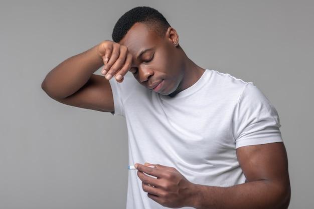 Hohes fieber, virus. dunkelhäutiger junger muskulöser mann, der die hand berührt, um traurig auf das thermometer zu schauen, das vor hellem hintergrund steht