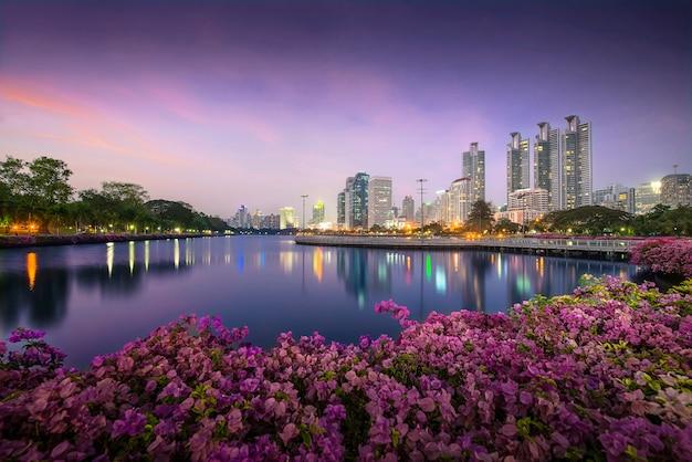 Hohes geschäftsgebäude hinter dem fluss im park in schöner nacht bangkok thailand