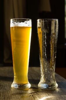 Hohes glas bier neben leerem glas auf holztisch im sonnenlicht