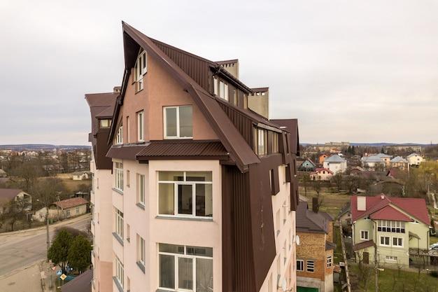 Hohes mehrfamilienhaus mit vielen fenstern und blechdach.