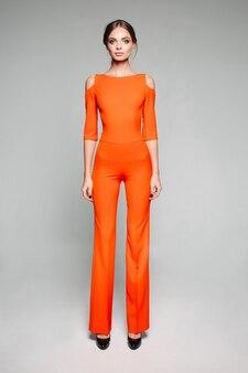 Hohes model in lässigem orange und high heels.