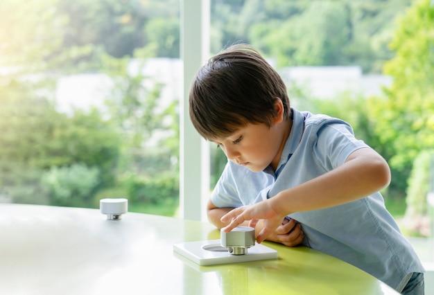 Hohes schlüsselporträt des schulkindes spiel im spielzimmer spielend, kind, das unteres spiel mit wunderndem gesicht in einem sonnigen raum nahe bei fenster hält, lernen und spielen, bildungskonzept