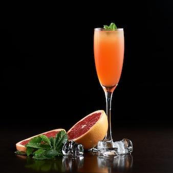 Hohes schmales kristallcocktailglas mit kaltem sommer erfrischendem orange saftigem getränk, grapefruitscheiben, frischen grünen minzblättern und transparenten eiswürfeln auf schwarzem hintergrund. bildseitenverhältnis 1: 1
